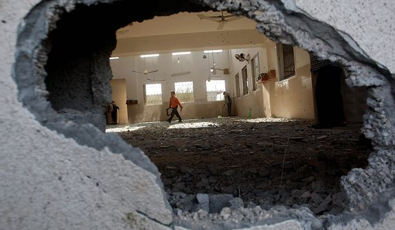 A Palestinian child walks through a damaged mosque after an Israeli airstrike in Beit Hanoun, northern Gaza, Friday, Nov. 16, 2012. (AP Photo/Hatem Moussa)