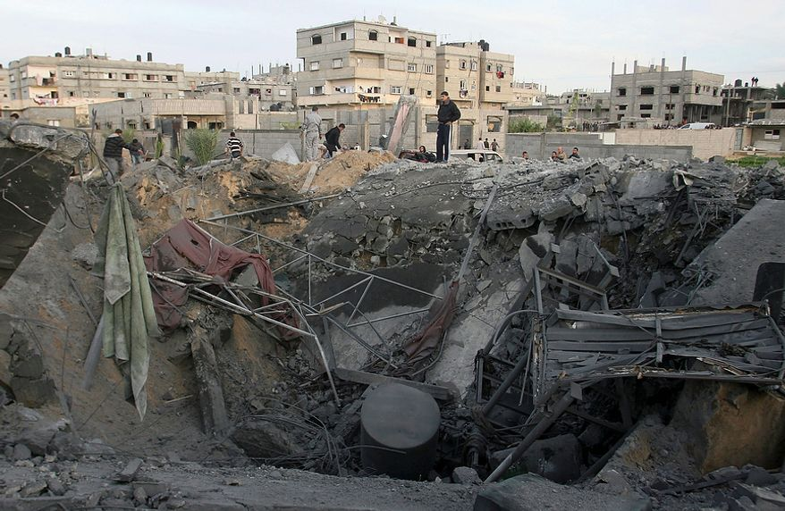 Palestinians stand on the rubble of the destroyed house of Hamas militant Mohammad Abu Shmala, following an Israeli air strike in Rafah, southern Gaza Strip, Friday, Nov. 16, 2012. (AP Photo/Eyad Baba)