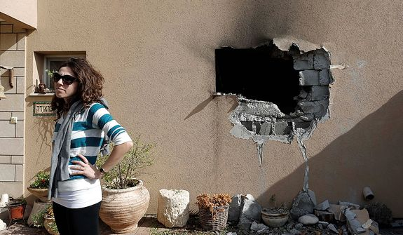An Israeli woman stands outside a damaged house hit by a rocked fired from the Gaza Strip that hit a house near the Israel-Gaza border, Friday, Nov. 16, 2012. Fierce clashes between Israeli forces and Gaza militants are continuing for the third day.(AP Photo/Tsafrir Abayov)