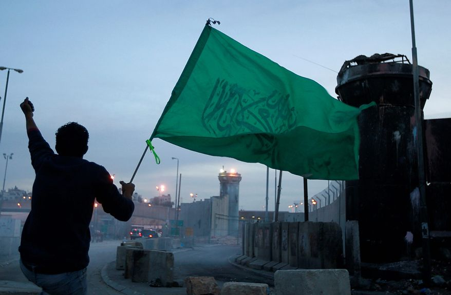 A Palestinian holds a green Islamic flag during clashes with Israeli troops at the Qalandia checkpoint between the West Bank city of Ramallah and Jerusalem, Friday, Nov. 16, 2012. (AP Photo/Majdi Mohammed)
