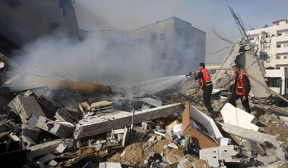 Palestinian firefighters try to extinguish a fire after an Israeli air strike on the building of Hamas' Ministry of Interior in Gaza City, Friday, Nov. 16, 2012. (AP Photo/Hatem Moussa)