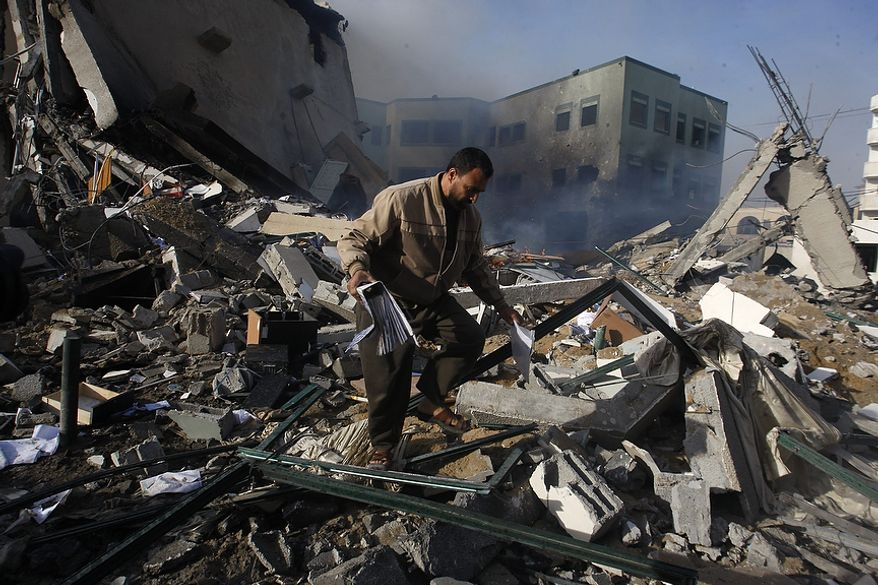 A Palestinian man picks up a binder from the debris after an Israeli air strike on the building of Hamas' Ministry of Interior in Gaza City, Friday, Nov. 16, 2012. (AP Photo/Hatem Moussa)