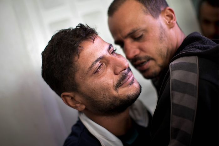 Palestinian Khaled Tafesh cries outside the morgue of Shifa Hospital before taking the dead body of his 10-month-old infant in Gaza City, Friday, Nov. 16, 2012. According to hospital reports, Haneen Tafesh died from wounds of an earlier Israeli strike. (AP Photo/Bernat Armangue)