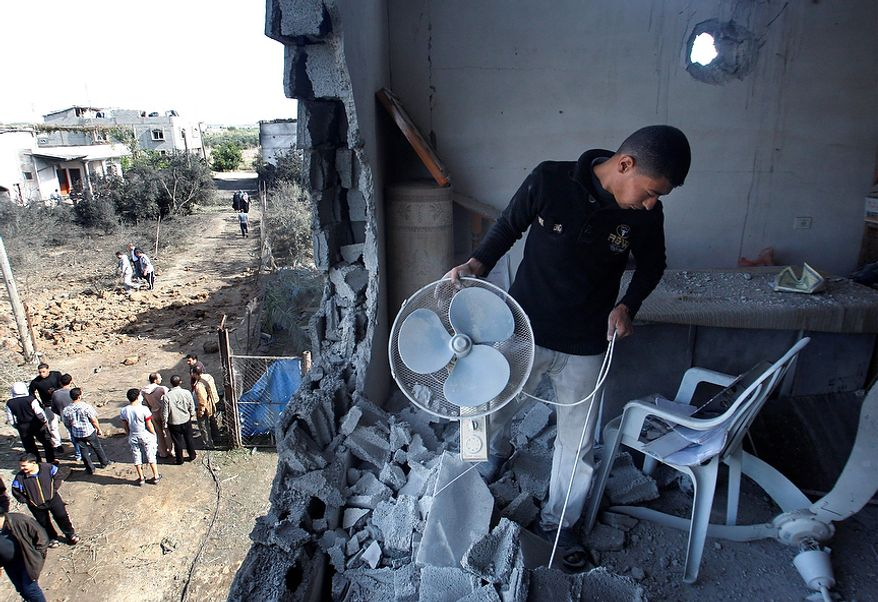 A Palestinian man inspects the damage to a mosque after an Israeli airstrike in Beit Hanoun, north Gaza, Friday, Nov. 16, 2012. Israel offered to suspend its offensive in the Gaza Strip on Friday during a brief visit by Egypt's premier there if militants refrain from firing rockets at Israel, an official said, but the Palestinians unleashed a fresh salvo. (AP Photo/Hatem Moussa)