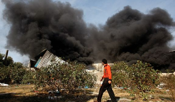 A Palestinian man walks past a fire after an Israeli airstrike on a wood factory in east Jabaliya, north Gaza, Friday, Nov. 16, 2012. Israel offered to suspend its offensive in the Gaza Strip on Friday during a brief visit by Egypt's premier there if militants refrain from firing rockets at Israel, an official said, but the Palestinians unleashed a fresh salvo. (AP Photo/Hatem Moussa)