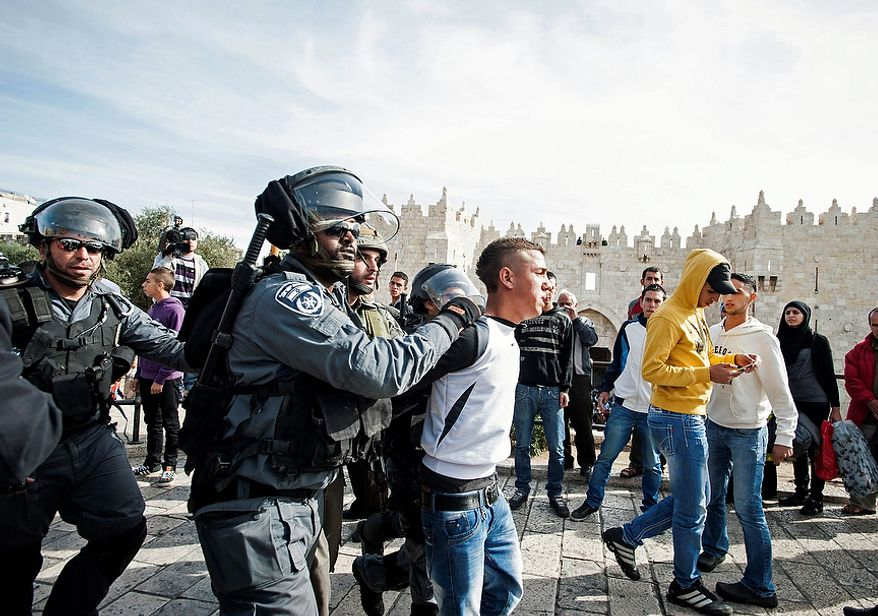 Israeli police detain a Palestinian demonstrator as scuffles broke out between Israeli troops and Muslim worshippers prevented from entering the Al-Aqsa mosque compound for prayers, Friday, Nov. 16, 2012. Israeli police was on high alert on Friday to prevent clashes following Friday prayers. (AP Photo/Omer Miron)