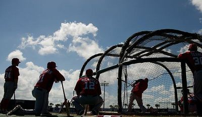 Washington Nationals right fielder Bryce Harper (34), left, Washington Nationals third baseman Ryan Zimmerman (11), second from left, Washington Nationals left fielder Jason Michaels (12), third from left, and Washington Nationals third baseman Mark Teahen (30), right, watch as Washington Nationals first baseman Michael Morse (38), second from right, takes batting practice during spring training at Space Coast Stadium, Viera, Fla., Wednesday, Feb. 29, 2012. (Andrew Harnik/The Washington Times)