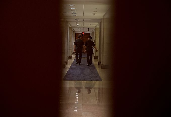 Two U.S. Capitol Police officers walk down a closed hallway in the Senate side of the Capitol Visitors Center while Gen. David Petraeus testifies about the Benghazi attack behind closed doors on Friday, Nov. 16, 2012. The general was expected to say that he knew the attack was terror-based from the beginning. (Barbara L. Salisbury/The Washington Times)