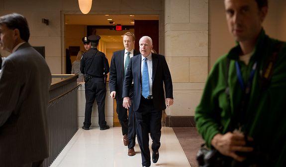 Sen. John McCain (R-Ariz.), center, heads to a closed door meeting with former CIA Director David Petraeus inside the Capitol Visitors Center on Capitol Hill, Washington, D.C., Friday, November 16, 2012. (Andrew Harnik/The Washington Times)
