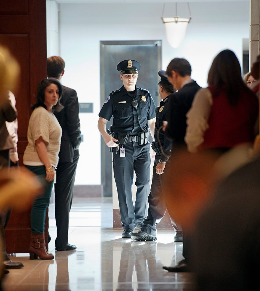 A Capitol Hill police officer stops people from entering a hallway on Capitol Hill in Washington, Friday, Nov, 16, 2012, near where the Senate Intelligence Committee was holding a closed-door hearing where former CIA Director David Petraeus testified on the Sept. 11, 2012 attack in Libya. (AP Photo/Cliff Owen)