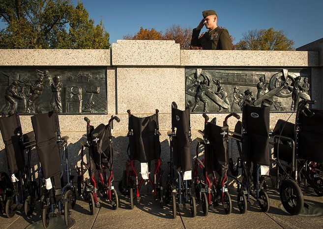 United States Marine Captain Wesley S. Jagoe [cq] salutes during the playing of the National Anthem above a row of wheel chairs used to assist a group of World War II  veterans as they arrive for the Veterans Day at the National World War II Memorial event in Washington, D.C., Sunday, Nov. 11, 2012. (Rod Lamkey Jr./The Washington Times)