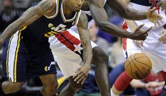 Utah Jazz's Mo Williams (5) and Washington Wizards' Emeka Okafor, right, chase after a loose ball during the first half of an NBA basketball game, Saturday, Nov. 17, 2012, in Washington. (AP Photo/Nick Wass)