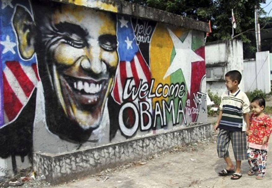 ** FILE ** Children walk near a graffiti painted by Myanmar artist Arker Kyaw to welcome U.S. President Obama on a street in Yangon, Myanmar, Nov. 17, 2012. (Associated Press)