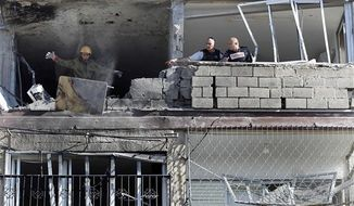 An Israeli soldier throws a blood-stained table from an apartment building hit by a rocket fired from the Gaza Strip, killing three people in Kiryat Malachi, southern Israel, Thursday, Nov. 15, 2012. (AP Photo/Tsafrir Abayov)