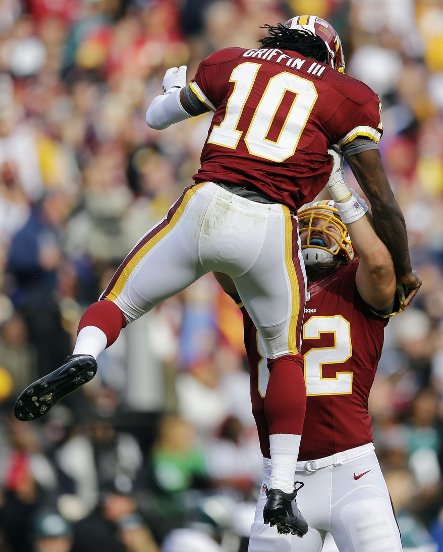Washington Redskins quarterback Robert Griffin III is picked up by tight end Logan Paulsen after Griffin threw a touchdown pass to wide receiver Aldrick Robinson during the first half of an NFL football game against the Philadelphia Eagles in Landover, Md., Sunday, Nov. 18, 2012. (AP Photo/Patrick Semansky)