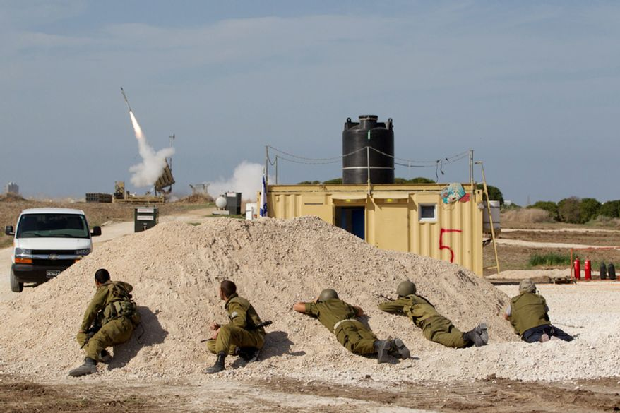 ** FILE ** Israeli soldiers look at an Iron Dome missile as it launched near the city of Ashdod, Israel, to intercept a rocket fired by Palestinians militants from Gaza Strip,  Sunday, Nov. 18, 2012. (AP Photo/Ariel Schalit)