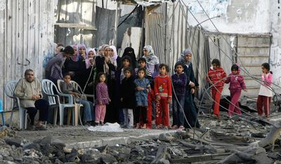 Palestinians stand near the rubble of the building of Attia Abu Inkara, a Hamas militant leader, following an Israeli air strike in Rafah refugee camp in southern Gaza Strip. (AP Photo/Eyad Baba)