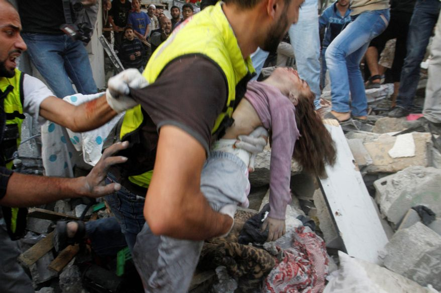 An emergency rescue worker carries a child's body found in the Daloo family house rubble following an Israeli air strike in Gaza City. Palestinian medical officials say at least 10 civilians, including women and young children, have been killed in an Israeli airstrike in Gaza City. (AP Photo/Hatem Moussa)