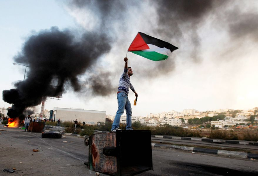 A Palestinian man waves national flag during a protest against Israel's operations in Gaza Strip, outside Ofer, an Israeli military prison near the West Bank city of Ramallah. (AP Photo/Majdi Mohammed)