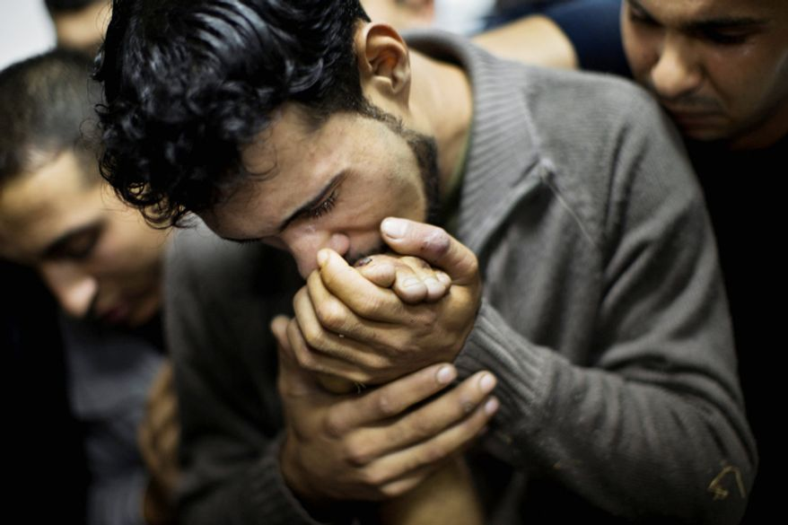 A Palestinian man kisses the hand of a dead relative in the morgue of Shifa Hospital in Gaza City. President Barack Obama on Sunday defended Israel's airstrikes on the Gaza Strip, but he warned that escalating the offensive with Israeli ground troops could deepen the death toll and undermine any hope of a peace process with the Palestinians. (AP Photo/Bernat Armangue)