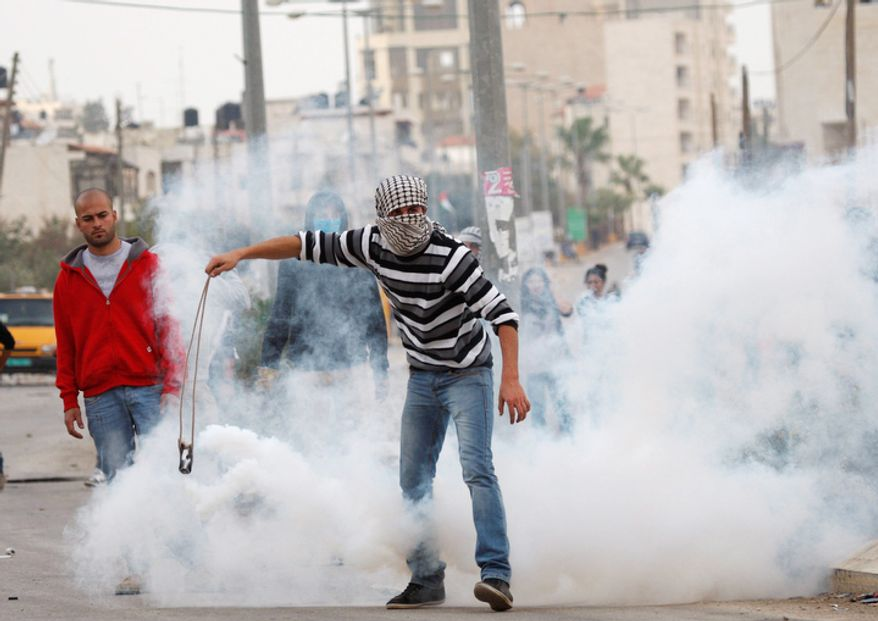 A Palestinian tries to throw back tear gas canister during a protest against Israel's operations in Gaza Strip, outside Ofer, an Israeli military prison near the West Bank city of Ramallah. (AP Photo/Majdi Mohammed)