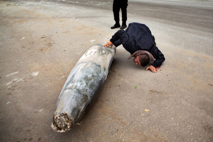 **FILE** A Hamas officer inspects an unexploded Israeli bomb in Gaza City on Nov. 17, 2012. Israel bombarded the Hamas-ruled Gaza Strip with more than 180 airstrikes, the military said, widening a blistering assault on militant operations to include the prime minister's headquarters, a police compound and a vast network of smuggling tunnels. (Associated Press)