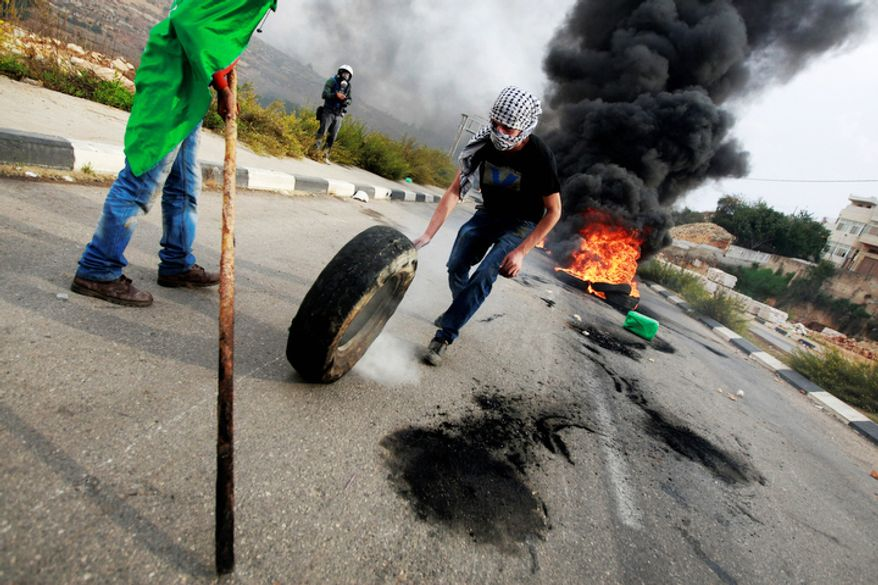 A Palestinian rolls a tyre against Israel's operations in Gaza Strip, outside Ofer, an Israeli military prison near the West Bank city of Ramallah. (AP Photo/Majdi Mohammed)