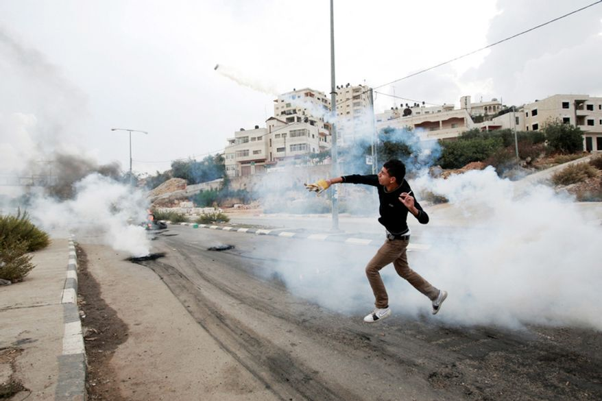 A Palestinian throws back a tear gas canister  during a protest against Israel's operations in Gaza Strip, outside Ofer, an Israeli military prison near the West Bank city of Ramallah. (AP Photo/Majdi Mohammed)