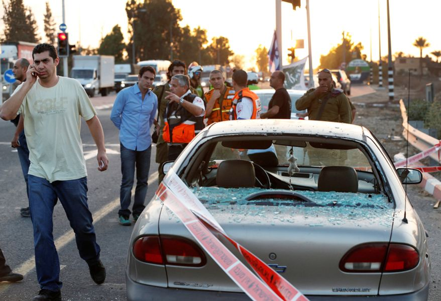 Israeli paramedics, military, and police gather  around a car that was hit by shrapnel from a missile fired by Palestinian militants from inside the Gaza Strip, and landed near the community of Ofakim, in southern Israel.   (AP Photo/Lefteris Pitarakis)