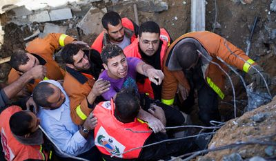 Osama Abdel Aal is rescued after his family house collapsed during an Israeli forces strike in the Tufah neighborhood, Gaza City, Sunday, Nov. 18, 2012. (AP Photo/Bernat Armangue)