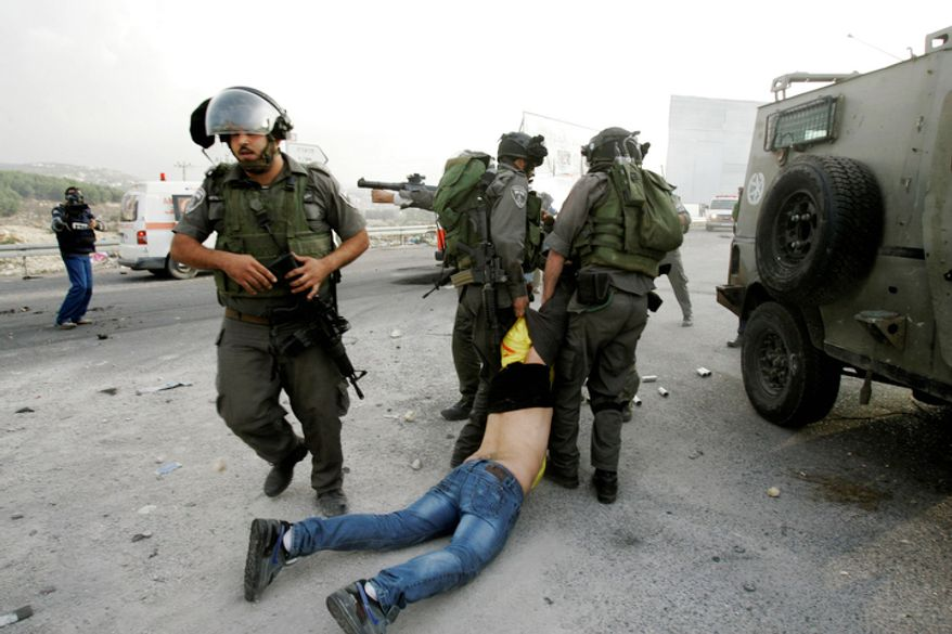 A Palestinian is arrested by Israeli security forces during a protest against the Israeli military operations in Gaza Strip near the West Bank city of Nablus. (AP Photo/Nasser Ishtayeh)