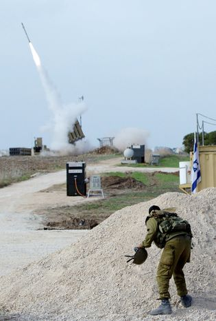 An Israeli soldier looks at an Iron Dome missile as it launched near the city of Ashdod, Israel, to intercept a rocket fired by Palestinians militants from Gaza Strip,  Sunday, Nov. 18, 2012.  Israeli strikes hit two media centers in the Gaza Strip on Sunday, as Israel warned it was widening its range of targets to go after military commanders of the territory's Hamas rulers. (AP Photo/Ariel Schalit)