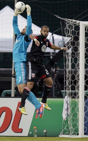 Houston Dynamo's goalkeeper Tally Hall (1) catches the ball as DC United's Maicon Santos, right, plays the ball during the first half of the second game of an MLS soccer Eastern Conference final playoff series match on Sunday, Nov. 18, 2012, in Washington. The Dynamo advanced to their second straight MLS Cup final and fourth in seven years, tying DC United 1-1 Sunday for a 4-2 aggregate win in the Eastern Conference final. (AP Photo/Luis M. Alvarez)