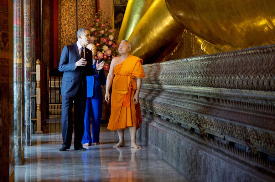 U.S. President Barack Obama, left, and U.S. Secretary of State Hillary Rodham Clinton, rear, tour the Viharn of the Reclining Buddha with Chaokun Suthee Thammanuwat, the Dean, Faculty of Buddhism Assistant to the Abbot of Wat Phra Chetuphon at the Wat Pho Royal Monastery in Bangkok, Thailand. (AP Photo/Carolyn Kaster)