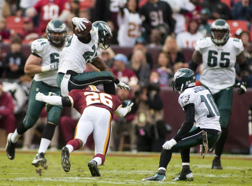 Washington Redskins cornerback Josh Wilson (26) dives for Philadelphia Eagles running back LeSean McCoy (25) in the second half, Landover, Md., Sunday, November 18, 2012.  (Craig Bisacre/The Washington Times)