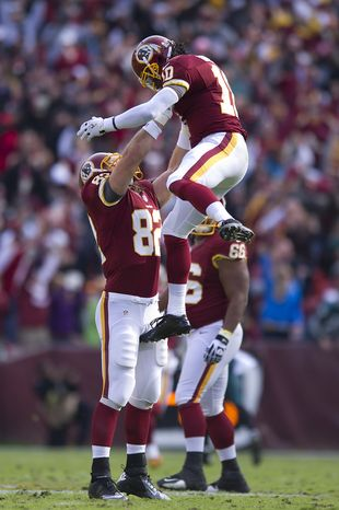 Washington Redskins tight end Logan Paulsen (82) lifts  quarterback Robert Griffin III (10) to celebrate a 49-yard touchdown pass to wide receiver Aldrick Robinson in the second quarter at FedEx Field, Landover, Md., Nov. 18, 2012. (Preston Keres/Special to The Washington Times)
