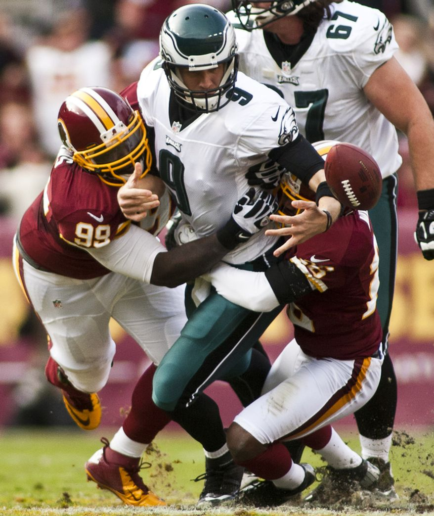 Washington Redskins defensive end Jarvis Jenkins (99) and cornerback Josh Wilson (26) force a fumble on Philadelphia Eagles quarterback Nick Foles (9) in the second half, Landover, Md., Sunday, November 18, 2012.  (Craig Bisacre/The Washington Times)