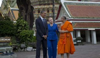 U.S. President Barack Obama, left, and U.S. Secretary of State Hillary Rodham Clinton, center, tour the Wat Pho Royal Monastery with Chaokun Suthee Thammanuwat, dean of the Faculty of Buddhism and assistant to the Abbot of Wat Phra Chetuphon, in Bangkok, Thailand, Sunday, Nov. 18, 2012. (AP Photo/Carolyn Kaster)