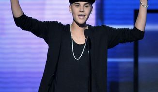 Justin Bieber accepts the award for favorite album - pop/rock for 'Believe' at the 40th Anniversary American Music Awards on Sunday, Nov. 18, 2012, in Los Angeles. (Photo by John Shearer/Invision/AP)