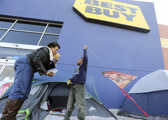 Denise Smith-Lad asks her grandson, Jordan Smith, 6, what he would like to eat as they camp in front of a Best Buy store in Cockrell Hill, Texas, on Monday. Mrs. Smith and her family lined up for the deals available on the day after Thanksgiving. (Associated Press)