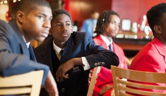 Among those listening to Kaya Henderson and Mayor Vincent C. Gray at Monday's luncheon at the Verizon Center is Anacostia High School's Markel Woods (left, in dark suit). (Craig Bisacre/The Washington Times)