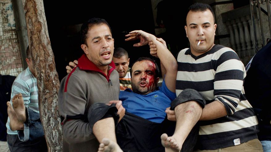 Palestinians carry the injured after an Israeli strike on a building in Gaza City on Monday. It was the second strike on the building in two days. (Associated Press)