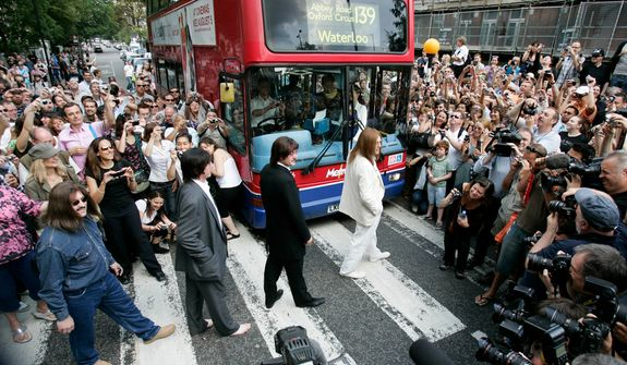 A tribute band dressed as members of British band, the Beatles, walk across the famous pedestrian crossing on Abbey Road, in London, in a recreation of the Beatles' Abbey Road album cover as hundreds of people  gathered to mark the 40th anniversary of the album, Saturday, Aug. 8, 2009. (AP Photo/Sang Tan)