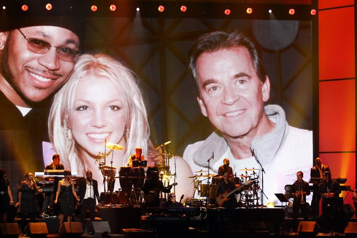 """Stevie Wonder and the Rickey Minor Band perform """"Master Blaster,"""" """"My Cherie Amour"""" and """"Sir Duke"""" during a tribute to Dick Clark as an image of Clark with Britney Spears and LL Cool J is displayed at the 40th Anniversary American Music Awards in Los Angeles on Nov. 18, 2012. (John Shearer/Invision/Associated Press)"""