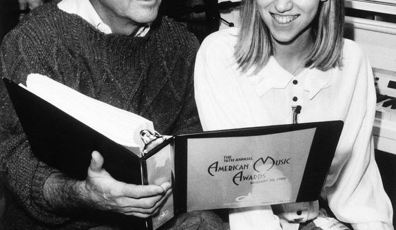 **FILE** Dick Clark and singer Debbie Gibson go over the script for the 16th annual telecast of the American Music Awards during rehearsals at Los Angeles' Shrine Auditorium on January 28, 1989. (Associated Press)