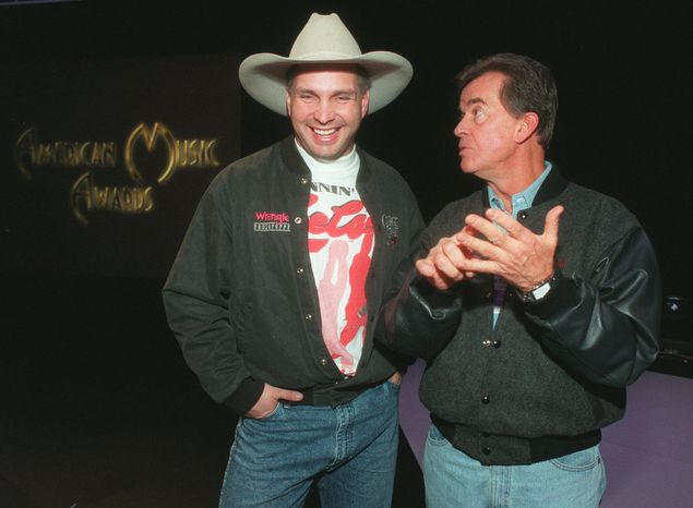 **FILE** Dick Clark (right) chats with country music singer Garth Brooks on Jan. 27, 1996, at the Shrine Auditorium in Los Angeles following a rehearsal of Brooks' performance for the American Music Awards. (Associated Press)