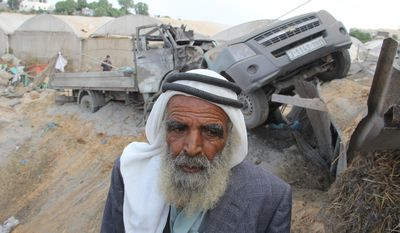 A Palestinian inspects damaged cars following an Israeli air strike in Rafah southern Gaza Strip, Monday, Nov. 19, 2012. (AP Photo/Hatem Omar)
