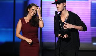 Justin Bieber accepts the award for artist of the year as his mom Pattie Malette looks on at the 40th Anniversary American Music Awards on Sunday, Nov. 18, 2012, in Los Angeles. (Photo by Matt Sayles/Invision/AP)