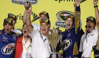 Team owner Roger Penske, third from left, and Brad Keselowski, second from right, celebrate after Keselowski won the NASCAR Sprint Cup Series championship following an auto race at Homestead-Miami Speedway in Homestead, Fla., Sunday, Nov. 18, 2012. (AP Photo/Alan Diaz)