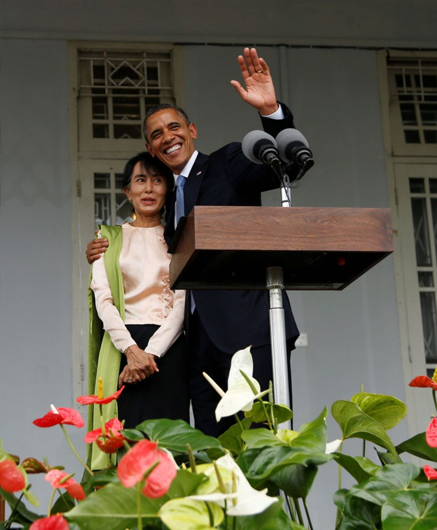 President Obama waves as he embraces Myanmar opposition leader Aung San Suu Kyi on Nov. 19, 2012, after addressing the media at her residence in Yangon, Myanmar. Obama, who touched down that morning, became the first U.S. president to visit the Asian nation also known as Burma. (Associated Press)